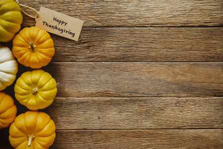 Happy Thanksgiving day background with pumpkins and greeting tag on wood table. Vintage style.