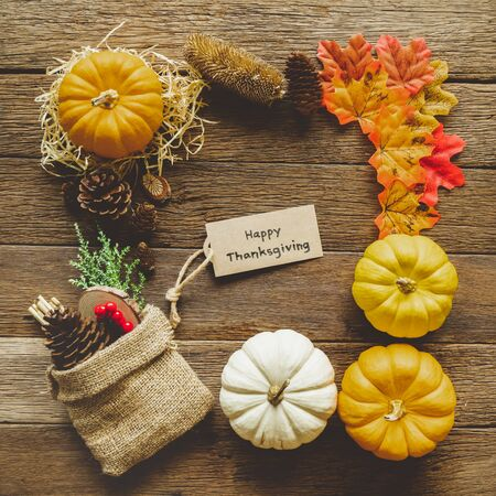 Autumn Thanksgiving day background from maple leaves, pumpkins, decorations frame on table wood vintage tone with red, orange, yellow and brown