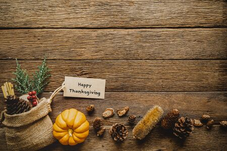 Happy Thanksgiving day background with pumpkin and greeting tag on wood table. Vintage style.