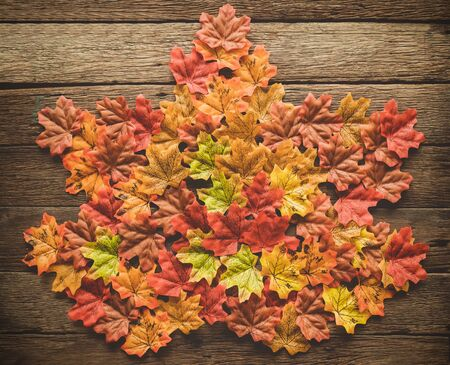 Autumn Thanksgiving day background from maple leaves on table wood vintage tone with red, orange, yellow and brown 스톡 콘텐츠