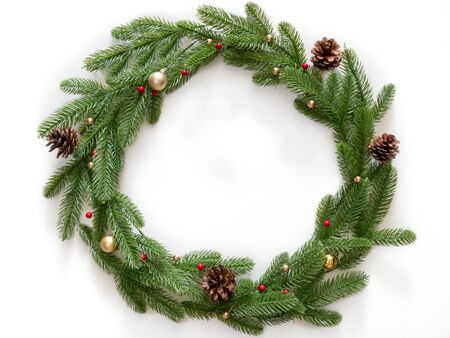 Christmas composition. Wreath made of christmas tree branches and pine cones with gold bubbles on white background. Flat lay, top view, copy space