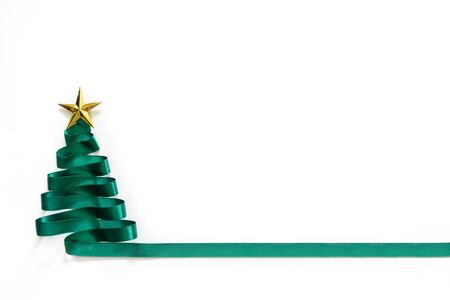 Christmas tree made from green ribbon with gold star on white background with copy space