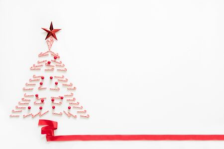 Christmas tree made from candy with red star and ribbon on white background with copy space