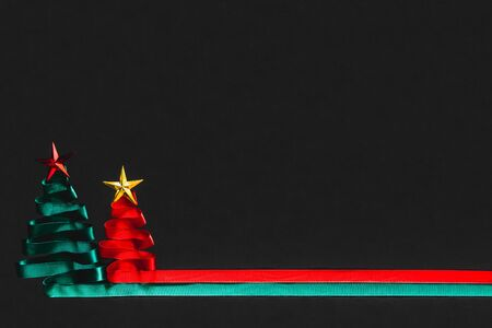 Christmas trees made from green and red ribbon with gold star on black background with coppy space