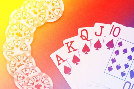 Royal Flush playing cards hand on colorful background with chips stack Stock Photo