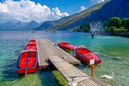 Red boats in summer time with swan in lake in Austria, Europe 版權商用圖片