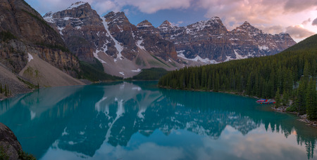 Panorama of The Moraine lake sunset with snow with turquoise lake and cloudy sunset sky, Banff, Alberta, Canada