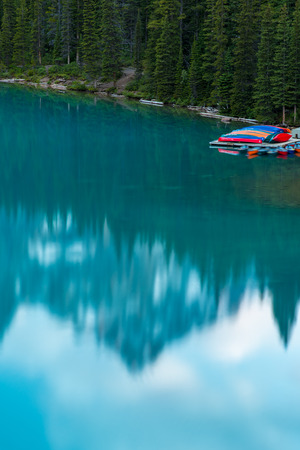 Vertical of The Moraine lake sunset with mountain reflection on the turquoise lake and bluesky, Banff, Alberta, Canada