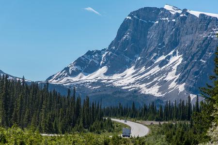 Viaggio su strada con una splendida vista della grande montagna e del cielo blu in Alberta, Canada.