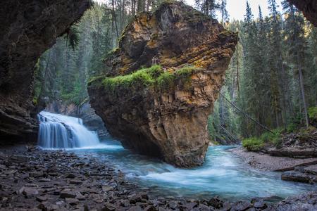 Johnston Canyon cave in Spring season with waterfalls, Johnston Canyon Trail, Alberta, Canada.