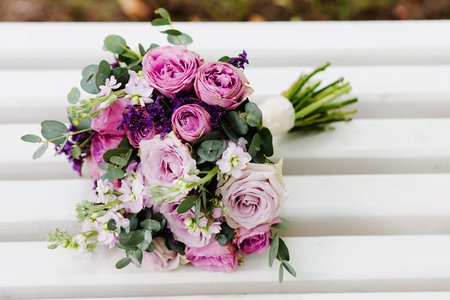 A purpule  wedding bouquet of flowers rests on a white bench Stock Photo