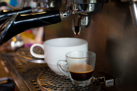 capucinno: coffee machine preparing fresh coffee and pouring  in cup Stock Photo