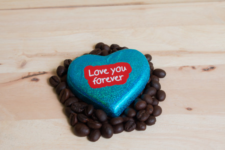 surrounded: Coffee beans surrounded Chocolate wrapper on Valentines Day, Wood background.