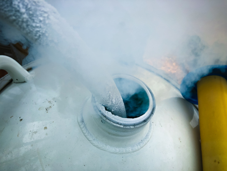 Close up of container with liquid nitrogen,Cold metal pipe smoking from transferring liquid nitrogen