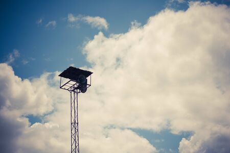 Old public loudspeakers broadcast on high tower with long distance tower Imagens - 131979881