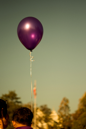 A purple balloon flying up in the sky.