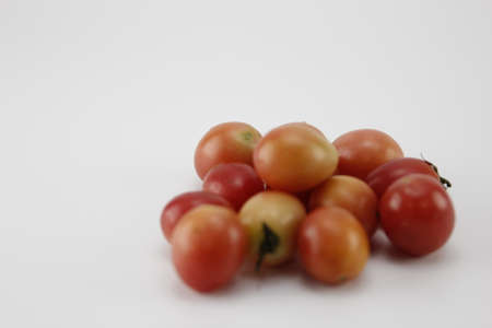Fresh tomatoes from the garden, laid on a white background.