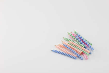 Multicolored birthday candles placed on a white background. Stok Fotoğraf