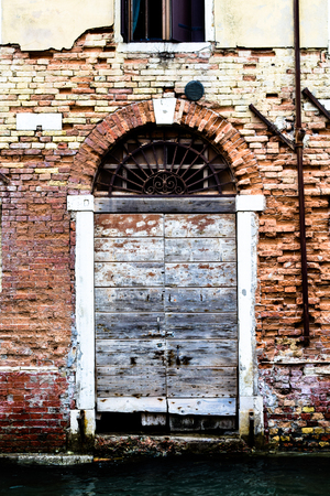 Dilapidated door opening onto a canal, Venice
