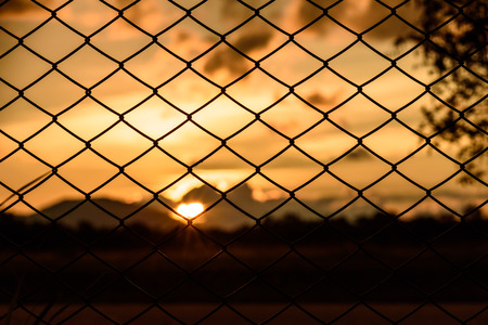 steel chain: sunset behind chain link fence