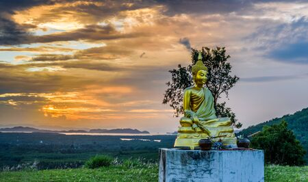over hill: ranong buddha sculpture over hill top in sunset Stock Photo