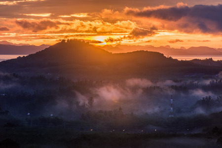 sunrise behind mountain and fog over forest