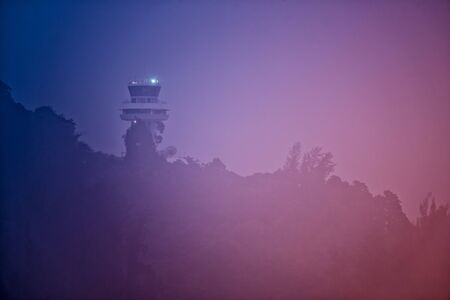Air traffic control tower in dense fog in evening