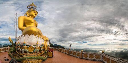 Great big golden buddha sculpture over hill at tiger cave temple Krabi, Thailand