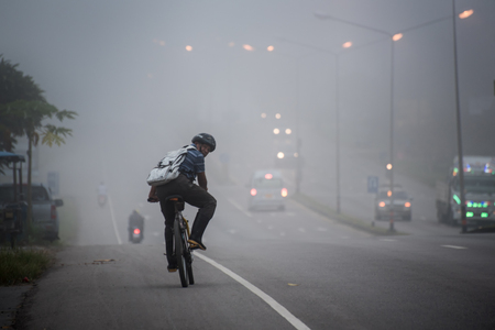 Krabi , Thailand ; October 7,2015. Man ride to work  in poor visibility road effect from Haze caused by forest fires in indonesia