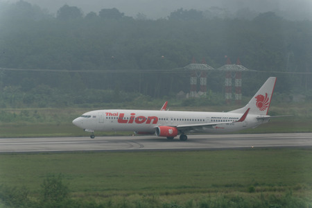 Krabi , Thailand ; October 6,2015. Thai lion air airline taxi in haze at Krabi airport late in morning effect from Haze caused by forest fires in indonesia Sajtókép