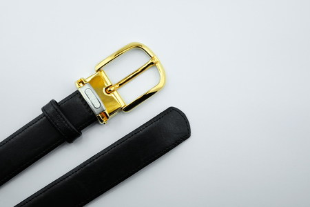 buckle: Gold buckle black leather strap on a white background.