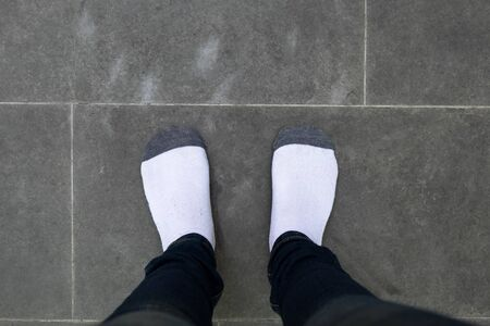 black pants: young girl with black pants and white sock standing on cement floor