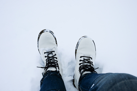 foot of woman with blue jean pants standing in snow floor Stock Photo