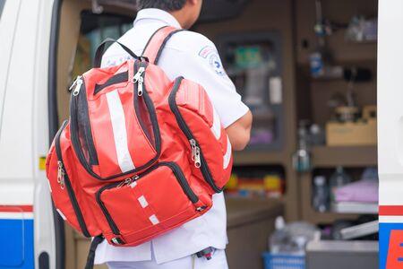 nursing unit: male nurse carry nursing bag on his back standing beside ambulance prepare for helping people