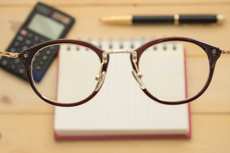 top view. focus at glasses have black calculator,black ballpoint pen, empty notebook paper are background. all of this putting on wooden. this image for business and education concept