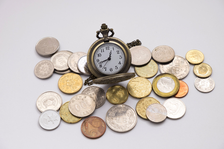 quite old silver pocket watch putting on various sizes coin stack with white background,this image for money saving and retro concept