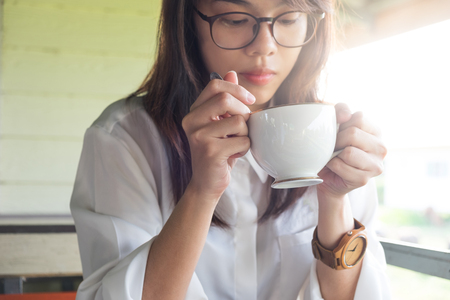 tea hot drink: young woman equip white shirt holding coffee cup and drinking hot coffee in morning time. this image for Stock Photo