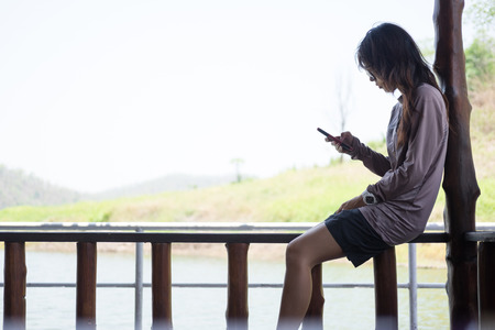 balcony: lonely young woman playing mobile phone while sitting wooden balcony on waterfront. this image for travel,portrait and technology