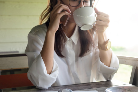 business woman talking on mobile phone while holding coffee cup with coffee for drinking in morning time. this image for business,people and portrait concept
