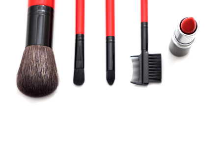 Brushes, red lipstick, eye pencil, and nail polish this all cosmetic accessory set putting on white background, this image for fashion and cosmetic concept