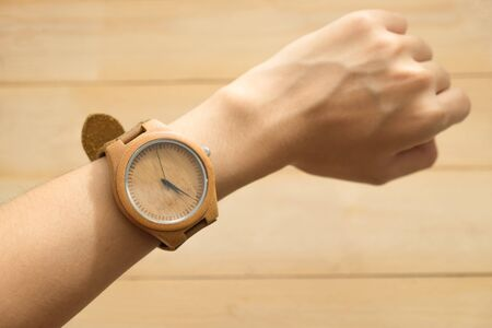 top view. business young woman equip wooden wrist watch on her arm have wooden are background. this image for equipment,accessory and fashion concept Stock Photo