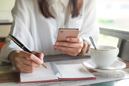 young woman equip white shirt using mobile phone for checking something while holding pen for writing on empty notebook and have coffee cup putting beside her. this image for bushiness,education and portrait concept Stock Photo