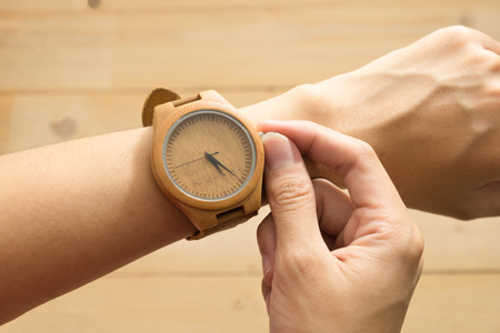 top view. business young woman equip wooden wrist watch on her arm and checking time. wooden are background. this image for equipment,accessory and fashion concept