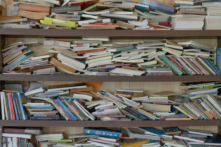 many messy book placed wooden shelf in library room. this image for library,education,wisdom ,interior concept Editorial
