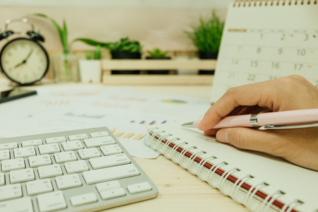 hand of women hold pen prepared for write on notebook has keyboard placed beside. with info graph, clock, calendar and many plants are background. image for business, work table, education concept Stock fotó