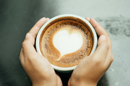 top view. young woman use hand both sides touch on side of the cup of coffee and has bubble a heart shape on top. image for coffee art, drink, beverage, body part, emotion concept