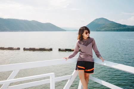 young asia woman stand alone at balcony front of her has sea, mountain, sky are background. this image for scenery, nature, travel, person, portrait, lanscape concept