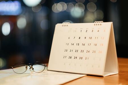 warmer Ton. Geschäftshintergrundkalender, Gläser und Reisekarte gesetzt auf Holztisch. dieses Bild für Reise, Zusatz, Mode, Geschäftskonzept Standard-Bild
