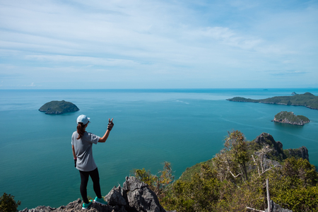 adventure sport background expressive young woman happy stand alone on top of mountain with sea. image for nature, journey, landscape, travel, success, extreme, concept  Stock Photo