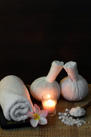 scented candle: Thai spa massage setting with towel, frangipani, herbal compress balls and bath salt on spoon